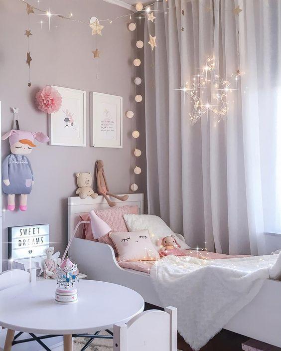 La guirlande étoiles la guirlande lumineuse le panneau lumineux le coussin rose le coussin blanc la lampe de chevet rose